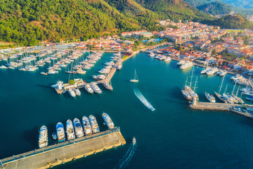 Aerial view of boats and yachts at sunset in Turkey. Colorful landscape with boats in marina bay, sea, mountains, forest, blue sky. Top view from drone of harbor with luxury yacht, sailboat. Travel