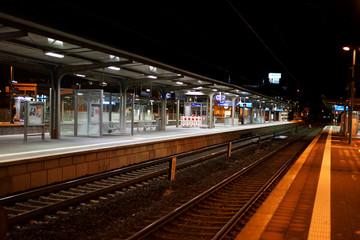 Bahnsteig mit Nachtbeleuchtung / Der Bahnsteig des Bahnhofes Weinheim in der Nacht mit Sitzplätzen, Schienen und Glasunterständen.