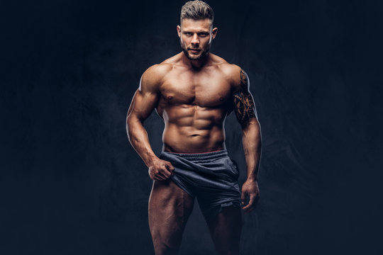 A handsome shirtless tattooed bodybuilder with stylish haircut and beard, wearing sports shorts, posing in a studio. Isolated on a dark background