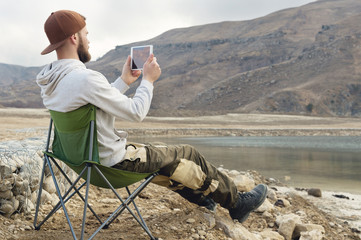 A bearded hipster in a cap sits on a folding chair on the shore of a high mountain lake and takes a photo on a tablet. A bearded blogger is broadcasting from nature. The concept of travel bloggers in