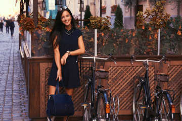 Smiling sexy brunette wearing stylish black dress in sunglasses, holds a black handbag, posing near bicycles against a background of a cafe.