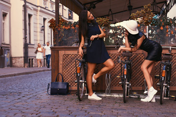 Two sexy brunette wearing stylish black dresses, posing near bicycles against a background of a cafe.