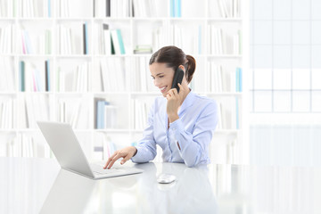 Business smiling woman or a clerk working at her office desk with computer and talk on the phone, contact us and support concept