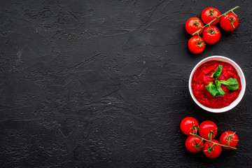 Tomato sauce in bowl with green basil near cherry tomatoes on black background top view space for text