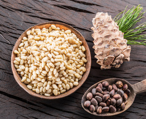 Pine nuts in the bowl and pine nut cone on the wooden table. Organic food.