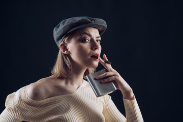 Blonde lady looks like suspicious detective. Detective concept. Girl thinking about investigation, holds flask and smoking cigar, copy space. Woman on mysterious face wears kepi, dark background.