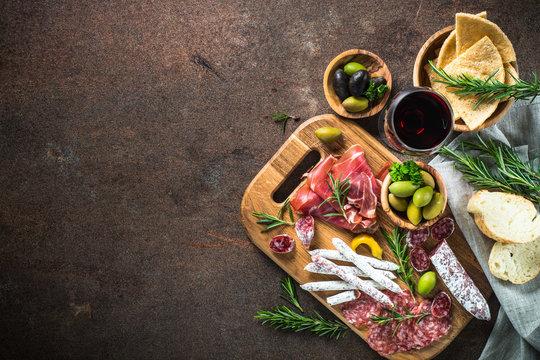Antipasto - sliced meat, ham, salami, olives and glass wine