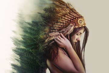 double exposure, beautiful woman with indian plume of plume and a forest on the head concept nature