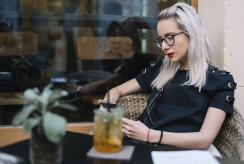 Young girl with glasses and white hair consumes soda in bar.