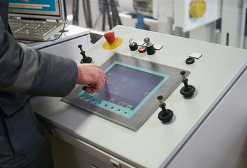 Engineer worker at control room touching sensor display controller. Portrait of a young technician worker in a factory. The operator monitors the work process from control room
