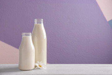 Two bottles of fresh milk on table against color background