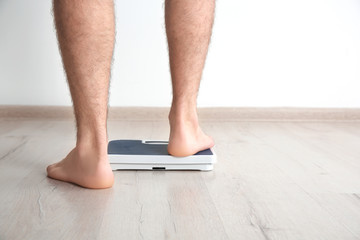 Overweight man measuring his weight indoors