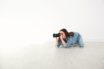 Female photographer with camera lying on floor indoors