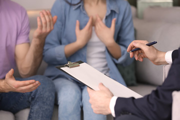 Family psychologist working with young couple in office, closeup