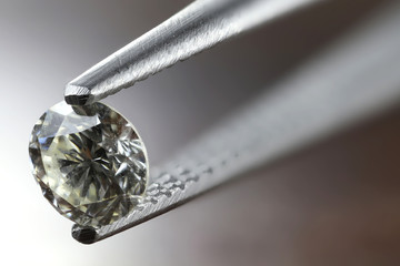 0.45 ct brilliant cut diamond held by tweezers