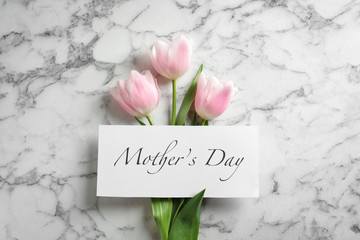 "Beautiful tulips and greeting card with words ""Mother's Day"" on marble background, top view"