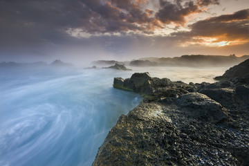 Breathtaking ocean sunset / Water whirlpool on amazing volcanic coast of south Iceland