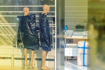 Two mannequins in an empty store window