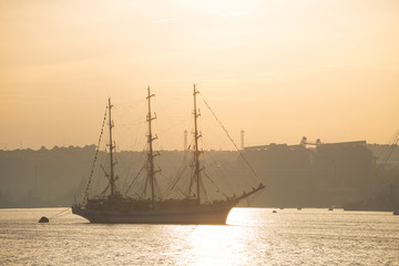 Three-masted sailing ship anchored in the port of Sevastopol at sunrise. Silhouettes of cargo port facilities and a warship on the background.