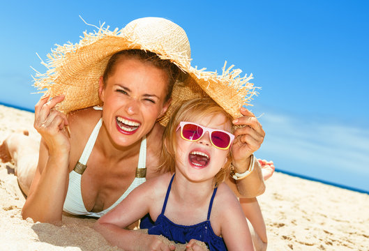 smiling modern mother and child in swimwear laying on seacoast