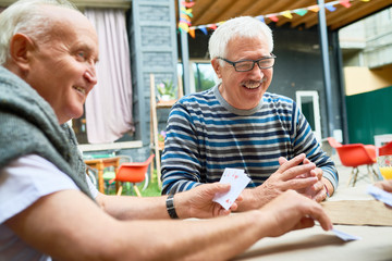 Portrait of two cheerful seniors playing card game at lunch table on outdoor terrace and laughing