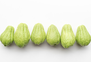 Directly above view of chayote or choko arranged in a row on a white table