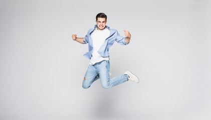 Full-length photo of funny man in casual t-shirt and jeans running or jumping in air isolated over white background