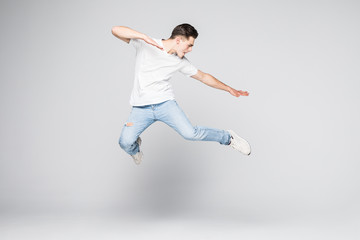 Cheerful young man jumping over white background