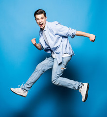 Handsome man jumping isolated on blue background