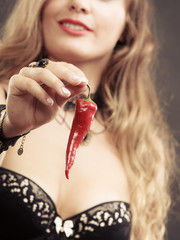 Woman wearing lingerie holding chilli pepper