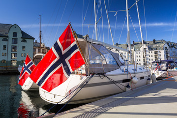 Yacht with the flag of Norway in Alesund town marina.