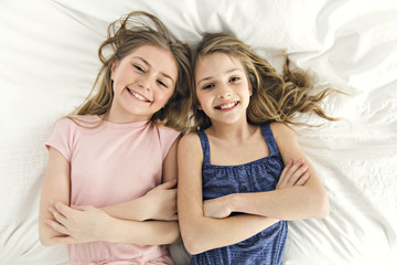 Portrait of two girls child friend in bed wearing pajamas