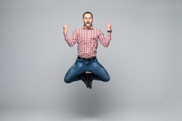 happiness, freedom, movement and people concept - smiling young man jumping in air isolated on white background