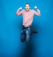 Young Bearded man in shirt which jumping on blue background