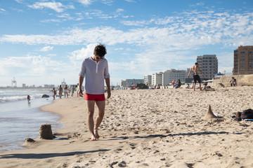 Man walking on the beach in swimwear