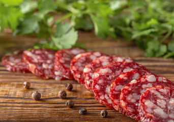 salami sausage with pepper and spices on a rustic wooden table, view from above