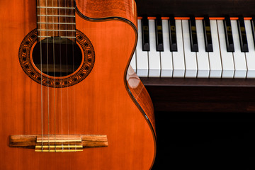 close up of classic guitar over grand piano keys for music background with copy space