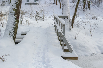Pedestrian bridge across the stream in winter under snow