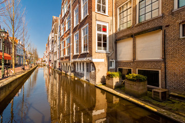 Fototapete - Historic buildings border a canal, along Voldersgracht street, in the old center of Delft, The Netherlands.
