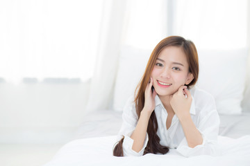 Beautiful portrait young asian woman lying and smile while wake up with sunrise at morning, lifestyle and relax concept.
