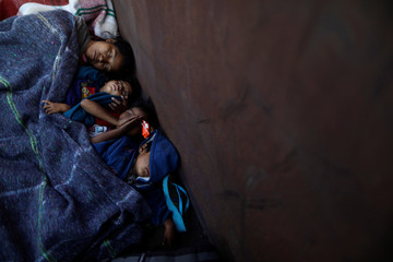 Central American migrants, moving in a caravan through Mexico, sleep as they travel in an open wagon of a freight train after stopping it on the rail line, in Michoacan state