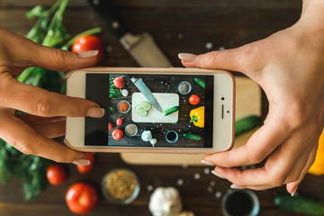 women's hands with a phone take pictures of vegetables