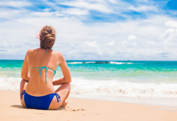 backview portrait of woman in bikini relaxing on tropical beach