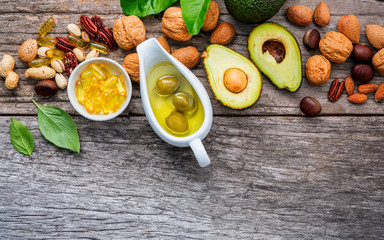 Selection food sources of omega 3 and unsaturated fats. Superfood high vitamin e and dietary fiber for healthy food. Almond,pecan,hazelnuts,walnuts,olive oil,fish oil and salmon on wooden background.
