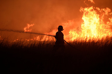 A firefighter works to control the Rhea fire near Seiling