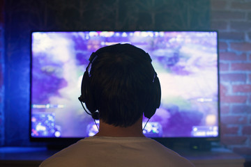 Gamer or streamer in earphones with microphone sits at home in dark room and plays with friends on networks in video games. A young man sits in front of a monitor or TV
