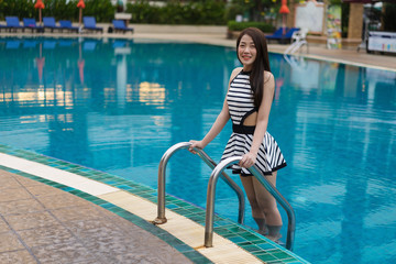 young woman standing on pool stairs
