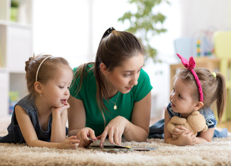 Young mother reading a book to her kids daughters. Children and mom lying on rug in cozy living room.