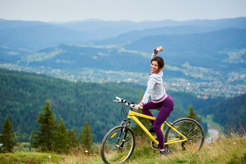 Beautiful female cyclist posing on yellow bicycle in the mountains on summer evening. Mountains, forests and small city on the blurred background. Outdoor sport activity. Copy space