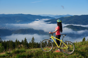 Side view of sporty female biker with yellow bicycle in the mountains, wearing helmet and red red t-shirt in the morning. Foggy mountains, forests on the blurred background. Outdoor sport activity